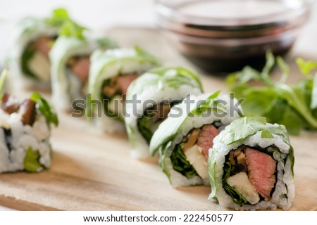 uramaki with sauce over wooden plate - stock photo