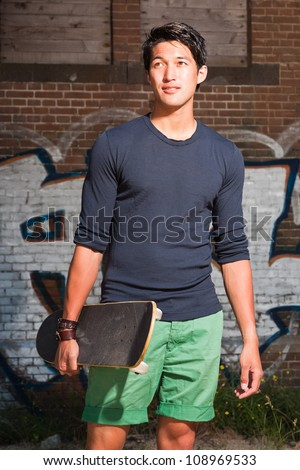 Urban asian man holding a skateboard. Good looking. Cool guy. Wearing dark blue shirt and green shorts. Standing in front of brick wall with graffiti. - stock photo