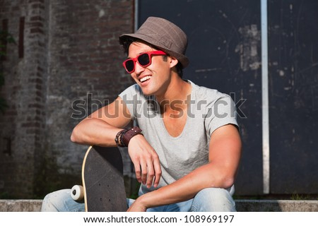 Urban asian man with hat, red sunglasses and skateboard sitting on stairs. Good looking. Cool guy. Wearing grey shirt and jeans. Old neglected building in the background. - stock photo