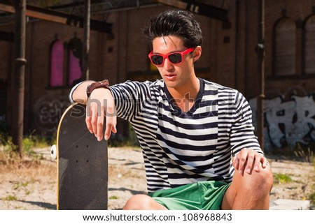 Urban asian man with red sunglasses and skateboard sitting on street. Good looking. Cool guy. Wearing blue white striped sweater and green shorts. Old neglected building in the background. - stock photo