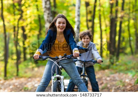 Urban biking - teens and bikes in city park  - stock photo