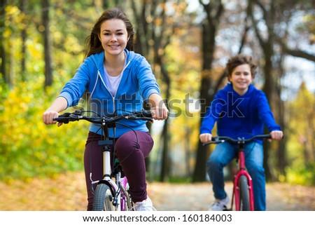 Urban biking - teens and bikes in city park  - stock photo