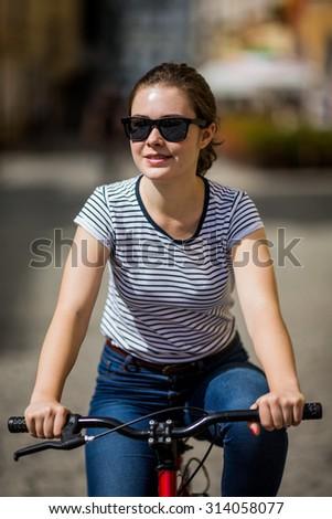 Urban biking - young woman and bike in city  - stock photo