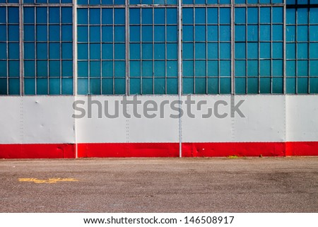 Urban Building Wall Texture of Airplane Hanger with Pavement, Wall and Windows - stock photo