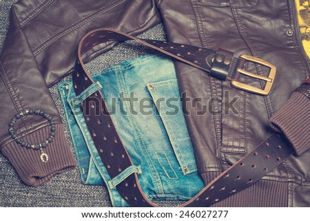 Urban fashion clothing: jeans with a belt, jacket, bracelet. Vintage style - stock photo
