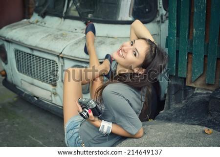 Urban girl has fun with vintage photo cameras outdoor near retro car, image toned. - stock photo