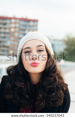 Urban girl with woolen cap kissing to camera in the city - stock photo