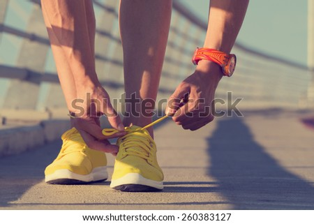 Urban jogger tying his running shoes on a big bridge. - stock photo