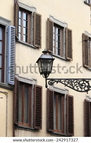 Urban landscape of Florence with old shutters and street lamp - stock photo