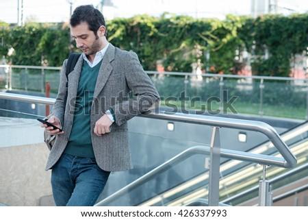 urban man calling on the phone near a metro station - stock photo