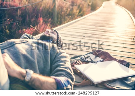 urban man lying on a catwalk in the field enjoying nature - stock photo