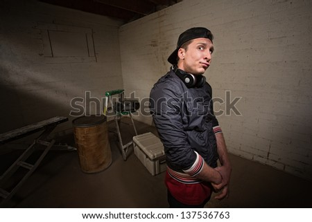 Urban musician with arms folded in basement - stock photo