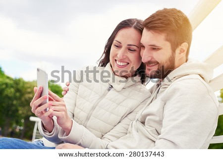urban photo of young adult couple looking at cellphone and smiling - stock photo