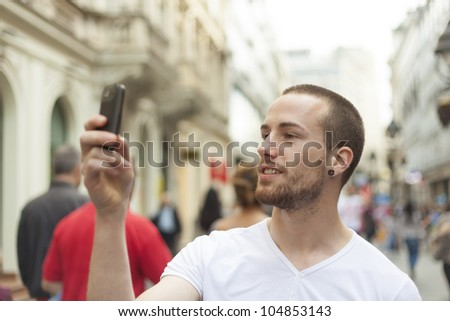 Urban photographer with mobila phone make photo on street - stock photo