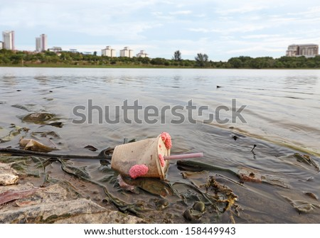 Urban plastic litter polluting a lake in a city park.  - stock photo