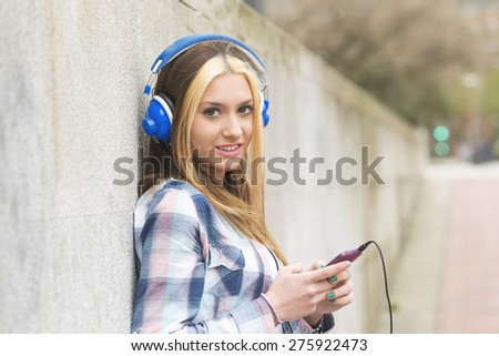 Urban portrait of cheerful beautiful girl listen music with headphones and smart phone in the street. - stock photo