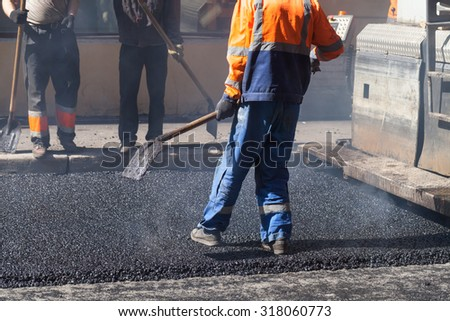 Urban road under construction, asphalting in progress, worker with a shovel in blue and orange uniform - stock photo