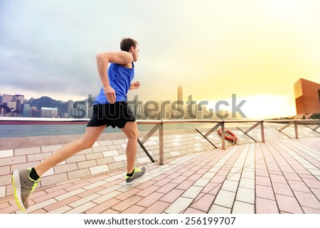 Urban running man runner in Hong Kong city skyline. Caucasian man working out jogging on the promenade of Victoria Harbor in HongKong, China, in afternoon sunset during spring. - stock photo