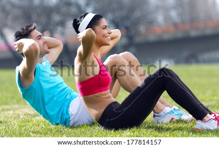Urban scene of Young couple doing push-ups - stock photo