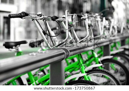 Urban scene with green bicycles for rent in a velo station - stock photo