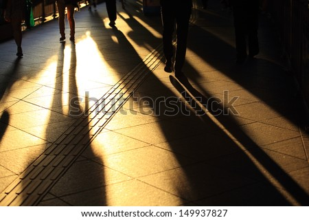 urban scenes: shadow of walking motion, pedestrian in the financial area at Hong Kong under sunshine - stock photo