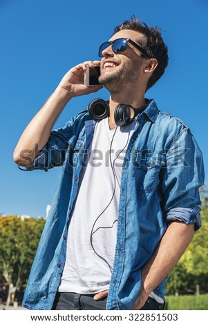 Urban smart casual handsome young man talking on smartphone. Happy male adult speaking on mobile phone. - stock photo