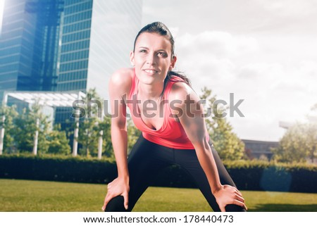 Urban sports - woman running for fitness in the city on beautiful summer day - stock photo