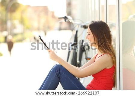 Urban teen girl using a tablet sitting in the street with a bicycle in the background - stock photo