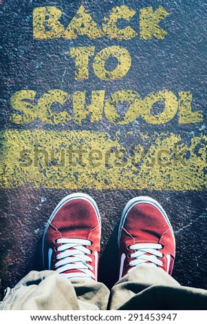 Urban teenage standing above the sign back to school - stock photo