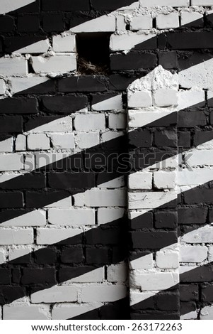 Urban view: brick wall roughly painted black and white, a bird nest in hole.  - stock photo