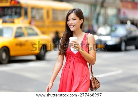 Urban woman drinking coffee happy smiling in New York City, Manhattan. Girl drinking hot drink from disposable cup walking in street wearing red dress. Biracial Asian Caucasian female model. - stock photo