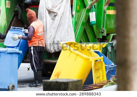 Urban worker municipal recycling garbage collector truck loading waste and trash bin - stock photo