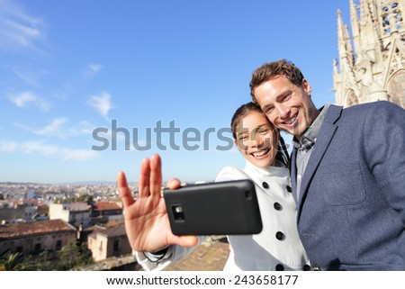 Urban young couple on travel in Barcelona taking selfie self portrait photograph with smart phone camera. Happy young man and woman in front of church in Barcelona, Spain. - stock photo