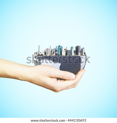 Urbanization concept with male hand holding globe and city on light blue background. 3D Rendering. Elements of this image furnished by NASA - stock photo
