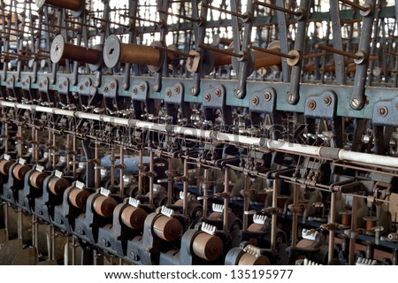 Urbex - textile industry, detail of old silk mill mechanism with bobbins, in light HDR processing - stock photo