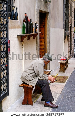 Urbino, Italy - May 27th, 2006: Old man with hat and cane sitting in front of a wine shop on a bench - stock photo