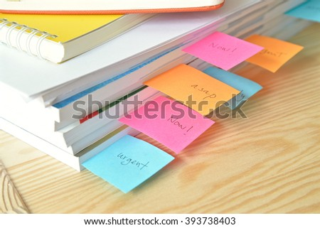 Urgent work with stack of document and sticky note at office - stock photo
