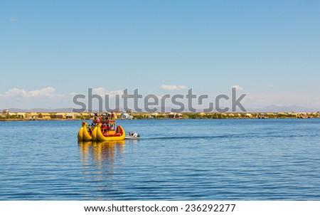 UROS ISLAND, PUNO, PERU: Reed boat in Titikaka lake closer Uros island, Puno, Peru. - stock photo