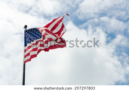 US American flag waving in the wind with beautiful blue cloudy sky in background - stock photo