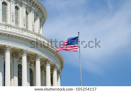 US Capitol Building dome detail with flapping US flag - Washington DC - stock photo
