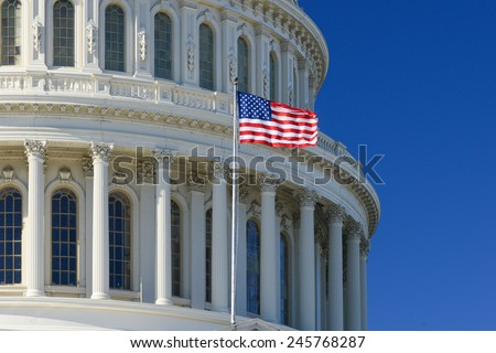 US Capitol Building dome detail with waving national flag - Washington DC, United States of America - stock photo