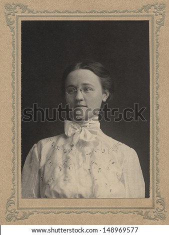 US - Circa 1895 - A vintage portrait of a woman school teacher about age 30,  posing for a portrait. She is dressed in the period style clothing. She is wearing round glasses with a chain. - stock photo