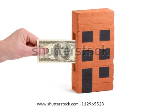 US Dollar bank note being inserted to or drawn from a block of flats - stock photo