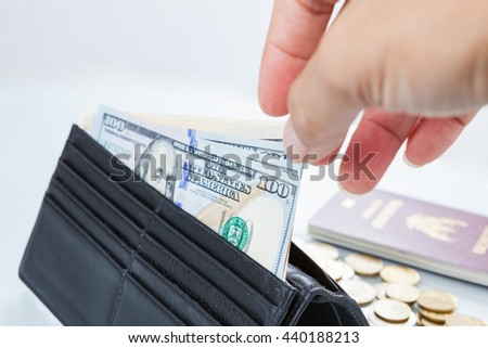 Us dollar banknote with Thailand passport in wallet on hand isolate on white Background. - stock photo