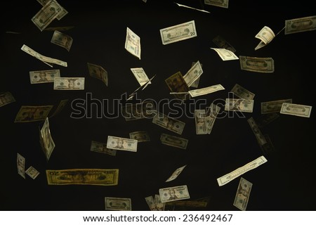 US Dollar bills falling to the ground lit from above and isolated over a black background - stock photo