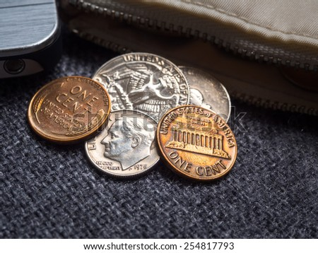 US dollar coins placed outside the wallet with smartphone. - stock photo