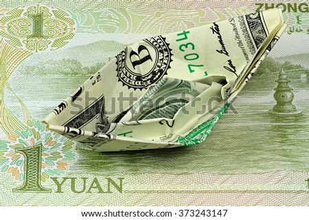 US Dollar paper boat on Chinese banknote - stock photo