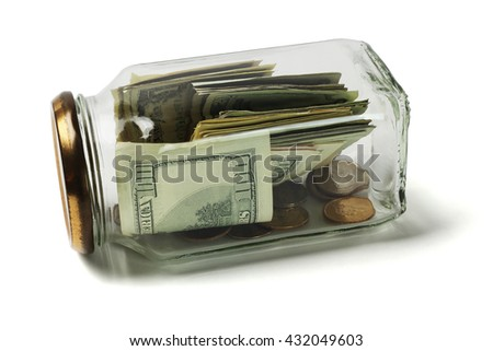 US Dollars and Coins in Glass Jar Lying on White Background - stock photo