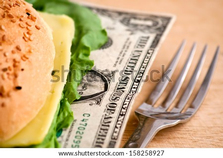 US dollars in a hamburger bun, close-up - stock photo