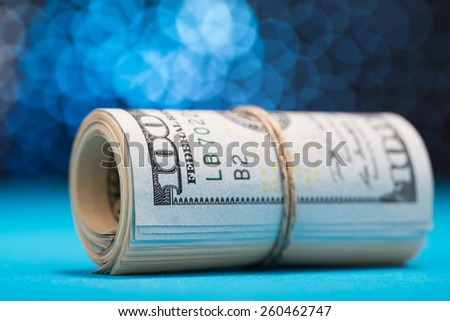 Us Dollars Rolled Up And Tightened With Band On Blue Bokeh Background - stock photo